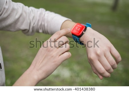 Girl hands touching the touch screen of the smart watch that she is wearing while she is doing sports