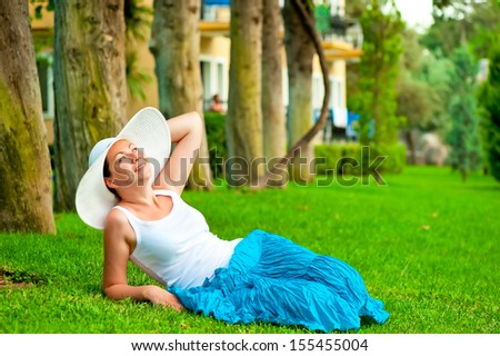 girl has a rest on a lawn in a hat and looking up at the sky - stock photo