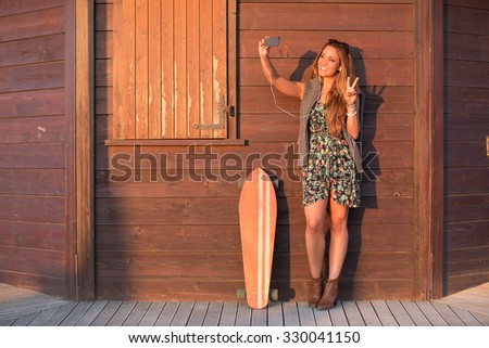 girl has fun clicking pictures while listening to music.hipster selfie woman snaps at sunset on a background of natural wood.concept of a girl who loves being outdoors, pauses after  longboard ride.   - stock photo