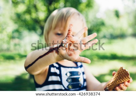 Girl has leaked ice cream on hand in closeup - stock photo