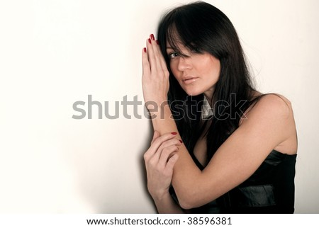 girl has leant faced to a hand near a white wall