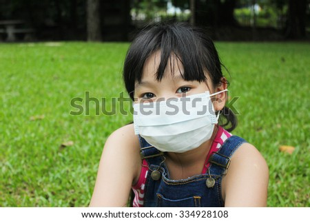 Girl have a fever and wear protection mask with green grass background. - stock photo