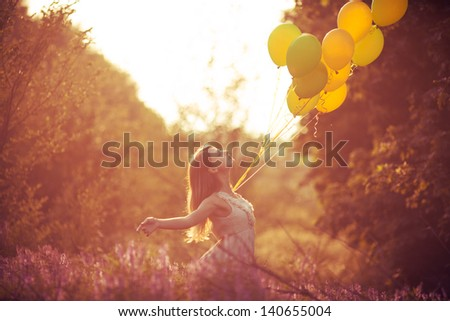 Girl have fun with yellow balloons at the sunset. Concept of freedom - stock photo
