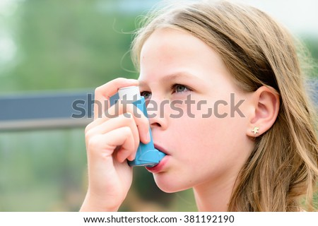 Girl having asthma using asthma inhaler for being healthy - shallow depth of field - stock photo