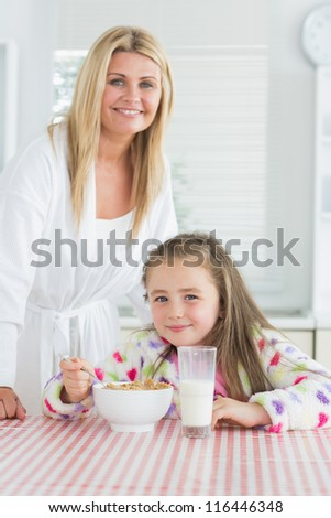 Girl having cereal for breakfast with mother in kitchen - stock photo