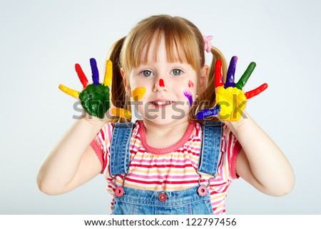 Girl having fun, her face and palms covered with paint