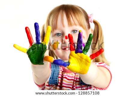 Girl having fun, her face and palms covered with paint - stock photo