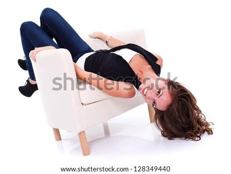 Girl having fun in the armchair, studio shot - stock photo
