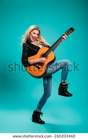 girl having fun in the studio with a guitar. musical instruments. concept. rock. blonde