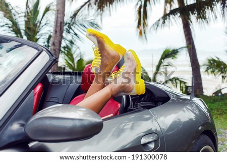 Girl having fun in tropical country laying in stylish luxury car in crazy bright clear boots. - stock photo