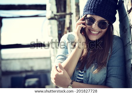 Girl having fun outdoors calling smart phone, lifestyle. Toned. - stock photo