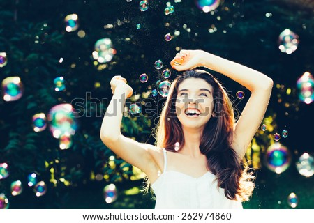 Girl having fun with bubbles - stock photo