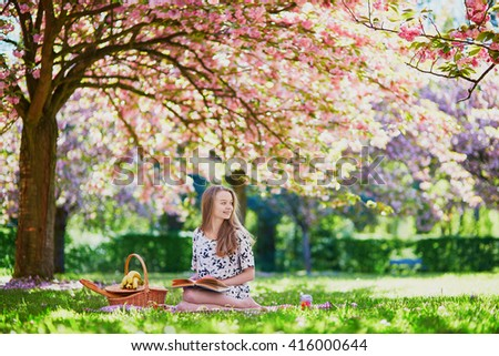 Girl having picnic and reading book in a beautiful cherry garden. Student preparing for exams or doing homework outdoors - stock photo