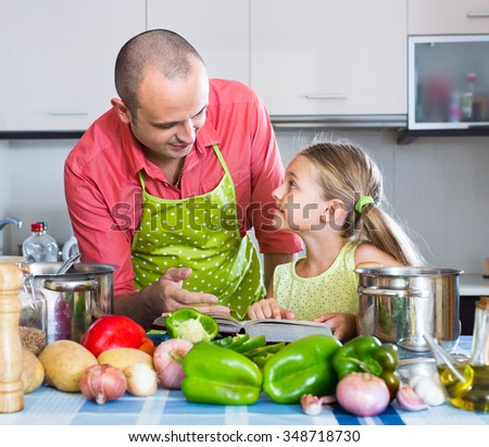 girl helping father to prepare dinner indoors - stock photo