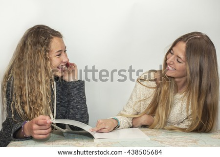 Girl helping little sister with her homework over a table map, in the room