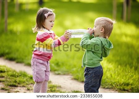 Girl helps boy to keep bottle - stock photo
