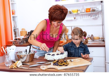 Girl helps her mother decorating the plum cake