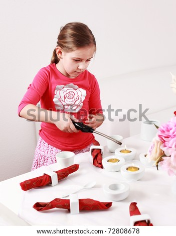 Girl helps to set the table - stock photo