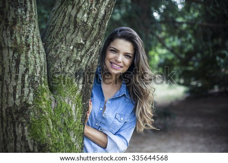 Girl hides behind a tree trunk - stock photo