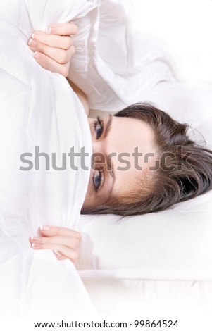 girl hides her face in bed