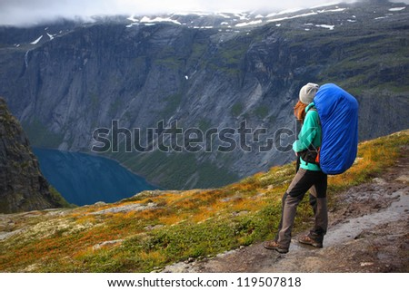 girl hiker are standing on a path and looking at the fjord - stock photo