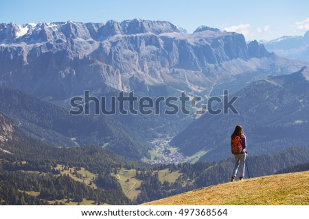 girl hiker at the mountains Dolomites and views of the valley, Italy. Seceda