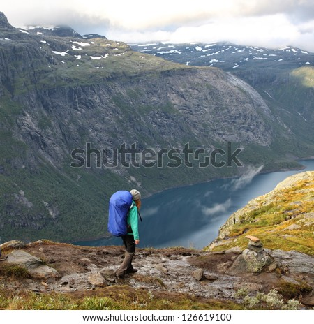 girl hiker going by path at the norwegian mountains - stock photo