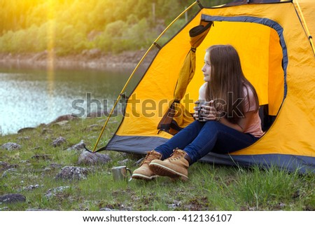 girl hiker in a tent and holding a cup mountains in the background, norway