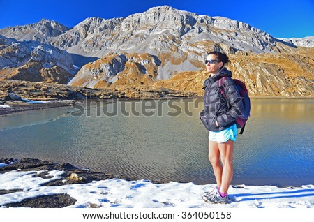 Girl hiker in the snow with dramatic backdrop of snow covered mountains and mountain lake, on a beautiful clear day - stock photo