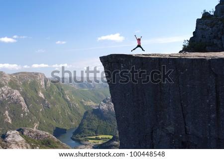 girl hiker jumping on Preikestolen, Preikestolen -famous cliff at the norwegian mountains - stock photo
