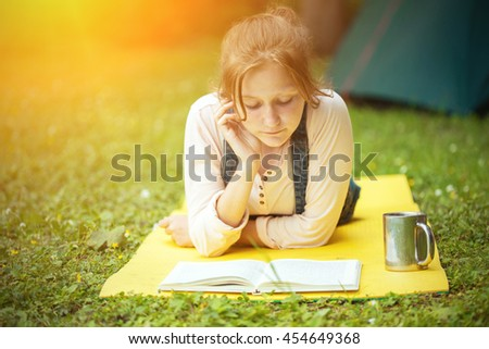 girl hiker lying and reading a book near the tent - stock photo