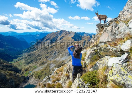 Girl hiker photographer ibex in the mountains on the rocks above a lake
