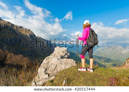 Girl hiker rests in the mountains during a walk and look at the landscape