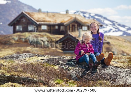 girl hiker sitting on a background of an old traditional wooden houses in Tyin, Norway  - stock photo