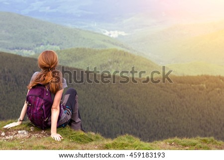 girl hiker with a backpack standing on the background of mountains and forests. Vorokhta - Ukrainian landscape.