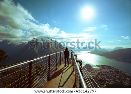 girl hiker with a backpack standing on  viewing platform and looking on Romsdalsfjorden and Andalsnes, Norway