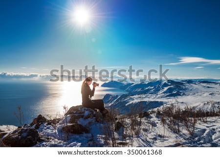 Girl hiker with a camera sits on top and photographing mountains in winter