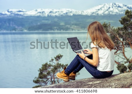 girl hiker with a laptop sitting on a rock on a background of mountains and lakes, norway