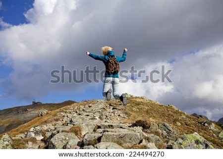 Girl hiker with backpacks jumping on top of a mountain with great valley view, Tatra mountains, Poland, Slovakia - stock photo