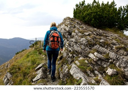 Girl hiker with backpacks standing on top of a mountain with great valley view, Tatra mountains, Poland, Slovakia