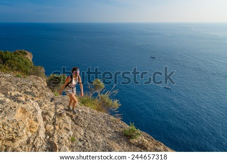 Girl hiking in the mountains above the sea - stock photo