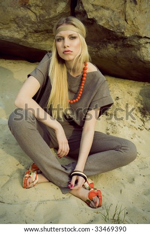 girl hippie sits on sand