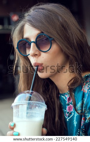 Girl hipster with glasses drinking milk shake. Outdoor lifestyle portrait of woman