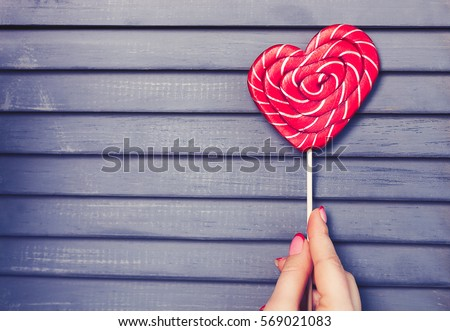 Girl hold heart shaped red candy on stick.Sweet decorative food for Saint Valentines Day celebration.Celebrate 14 February love with decorated sweets.Valentin Day background.Wooden holiday background