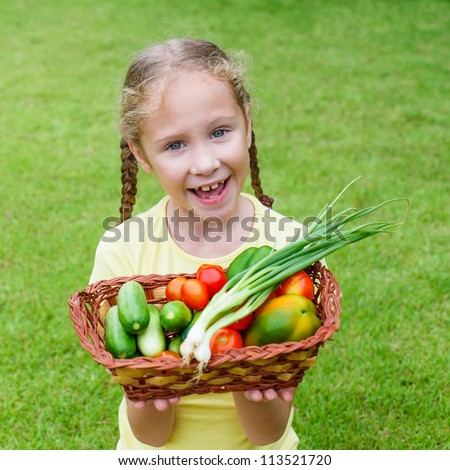 girl holding a basket of vegetables (cucumber, pepper, tomato, onion) - stock photo