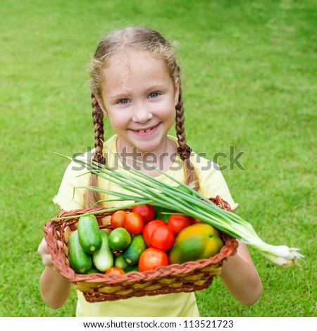 girl holding a basket of vegetables (cucumber, pepper, tomato, onion)