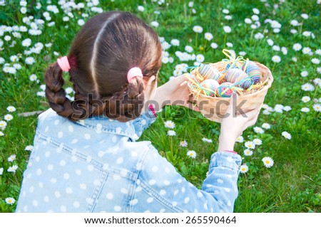 Girl holding a basket with easter eggs - stock photo