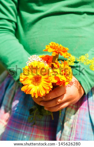 Girl holding a bouquet of orange flowers