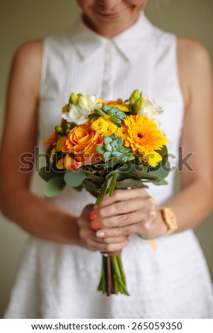 girl holding a bouquet of orange flowers in rustic style - stock photo