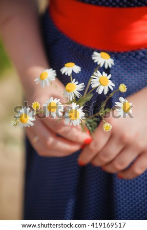 Girl holding a bouquet of wild daisies